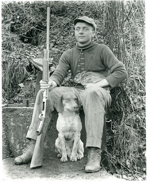 Paul Aegerter sitting with a rabbit on his lap and a gun in his hand.  A dog is sitting beside him.  Helvetia, W. Va.