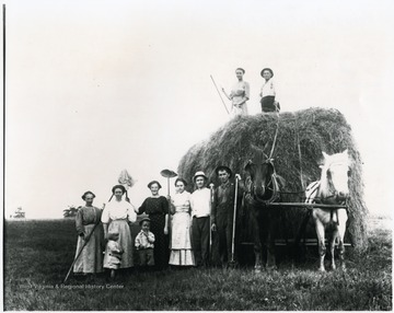 Group of people, some from the Aegerter family, standing with horses pulling a large bale. Helvetia, W. Va.