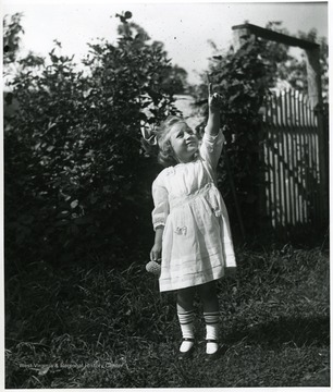 Child, Grace Holtkamp (Herrstrom), pointing toward the sky.  Helvetia, W. Va.
