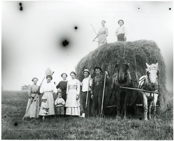 Making hay at the Aegerter's:  on the load, Nellie Schroth Aegerter, Louis Haslebacher, standing L-R Frieda Aegerter Stadler, unknown, Olga Aegerter Holtkamp, Lena Haslebacher Burky, Paul Aegerter,  unknown.  Children unknown.  Helvetia, W. Va.