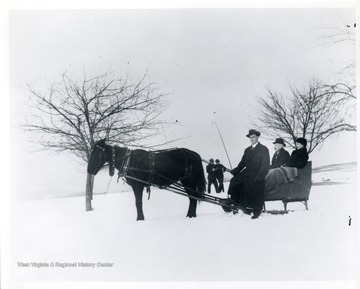 'In the sleigh right to left, Elka Hassig, Ernest Hassig, and Herman Schneider.'