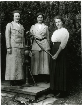 Olga Aegerter and two other women pose for a portrait next to a water pump in Helvetia.