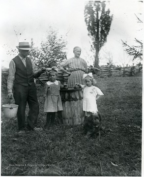 Gottfried and Marianne Aegerter with their grandchildren standing next to a barrel.