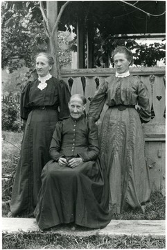 The three ladies are in dresses posing for a portrait outside.