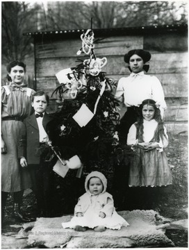 Children stand next to a Christmas tree.
