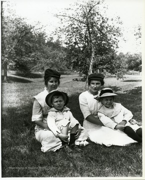 Two mothers holding small children while sitting in a field.