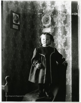 A young child is standing on a chair in a room in a house in Helvetia, West Virginia.