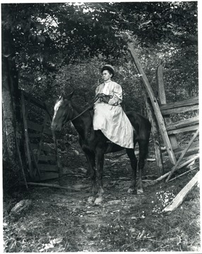 Woman sitting on a horse in a fenced in area by a forest.  Helvetia, W. Va.