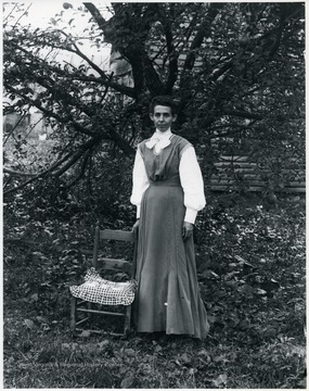 Women standing with a chair, tree in the background.  Helvetia, W. Va.