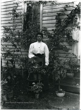 Dora Huber, Helvetia's sole African American woman standing behind a chair with potted plants.