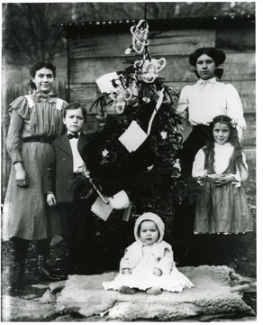 Baby Charles R. Shock seated in front of tree.  Bess and Herbert Shock standing to left of the tree.  Alma and Cinderilla (born August 30, 1901 and died June 3, 1991) Shock standing on right side of tree.