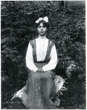 Young woman sitting on a chair with plants in the background, Helvetia, W. Va.