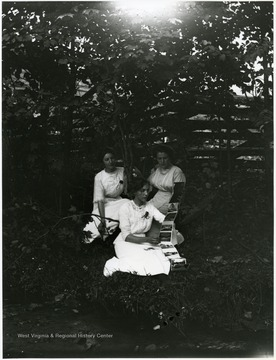 Three women sitting in forested area looking at postcard foldout book.  Helvetia, W. Va.
