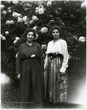 Two women standing in front of blossoming bush in Helvetia, W. Va.