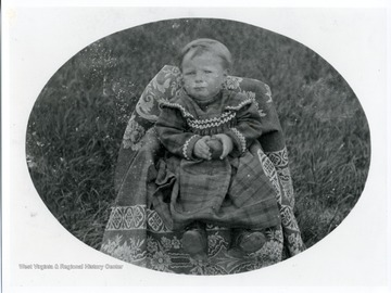 A young child holding an apple is sitting in a chair in a field.
