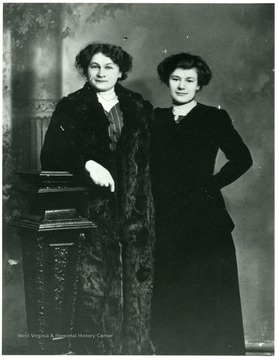 Two women (L- Babette Kolar Schneider R- a friend) standing together for a studio portrait.
