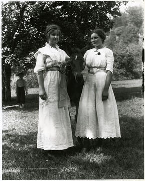 Two young women standing with a young horse in between them.  A young boy is standing in the background under a tree.  Helvetia, W. Va.