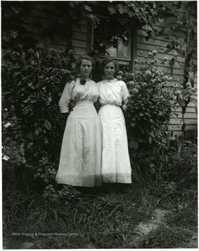 Two women standing together between blossoming dahlias, Helvetia, W. Va.
