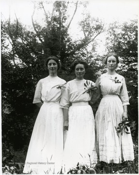 Three women standing together, small trees in the background, Helvetia, W. Va.