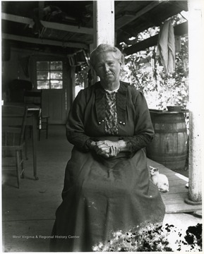 Older woman sitting alone on a porch.  Cat in the background.  Helvetia, W. Va.