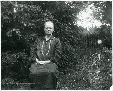 Older woman sitting in a fenced in brush area.  Helvetia, W. Va.