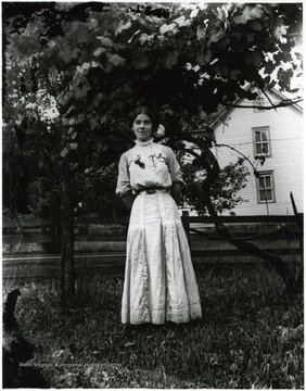 Young woman standing alone in front of a tree.  House in the background.  Helvetia, W. Va.