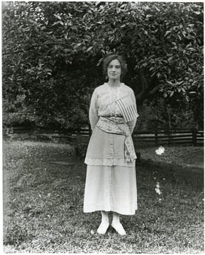 Young woman with a flag pinned to her dress standing alone in front of a tree in a fenced area.  Helvetia, W. Va.