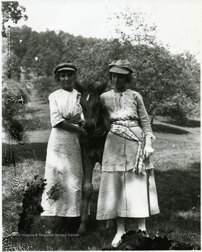 Two women standing with a young horse in between them.  Helvetia, W. Va.