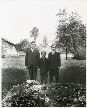 Three young boys wearing suits are standing in a field in Helvetia, West Virginia.