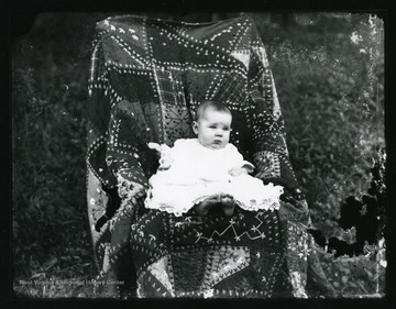 A young baby sitting in a chair which is covered with a quilt.