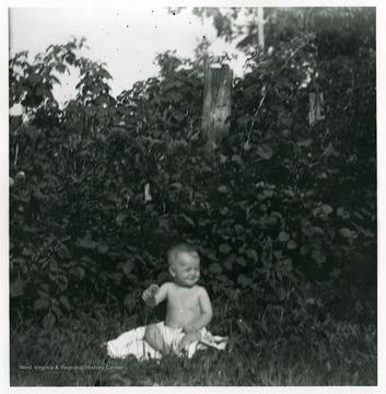 A baby is sitting on a blanket near some trees in grass in Helvetia, West Virginia.