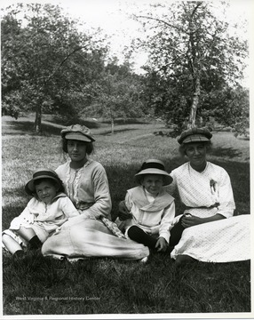 Two mothers are sitting with their children in a field near some trees.
