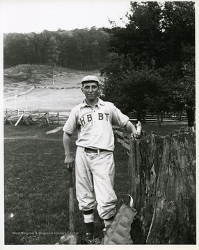 Arnold Metzener, a member of the Helvetia Baseball Team, is standing near a fence and holding a bat.
