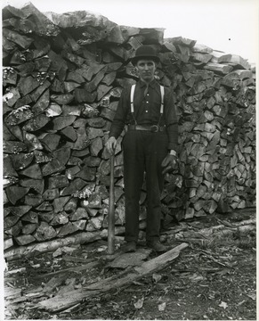 Arnold Metzner with baseball bat and glove standing in front of a large stack of firewood.