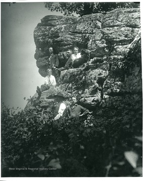 Five men and a boy are seating on a cliffside on Turkeybone Mountain, in Helvetia, West Virginia. Arnold Kuenzler is on the bottom, and Herman and Leo Stadler are also in the picture.
