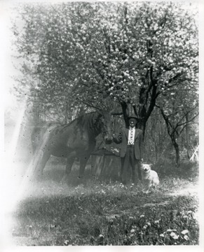 A man is standing with a horse and a dog under a tree near Helvetia, West Virginia.
