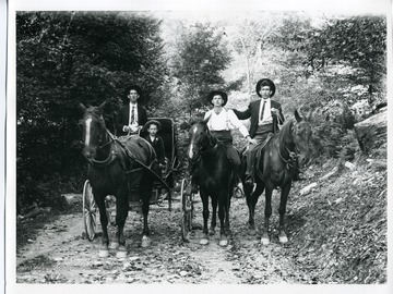 Two men are riding horses while another man and a young boy are riding in a horse drawn carriage down a dirt path.