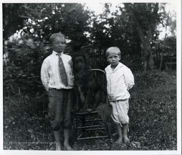 Herbert and Leo Stadler are standing next to a dog who sitting in a chair.