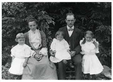Katharine Rohner Stadler and Walter Stadler are posing with their children Bertha, Louise, and Lydia near some trees.
