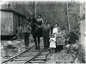 Man is holding horse's bridle in the center of picture with little boy riding the horse.  Lumber camp bunkhouses are visible at left.