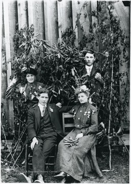 The two couples posed amongst shrubbery.
