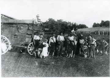 Group of men and children take a break for food and drinks after working with a threshing machine.
