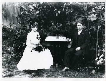 Clara Koerner and John Gobeli are sitting at a table. Clara is wearing a long white dress and is holding flowers while John is wearing a three piece suit.