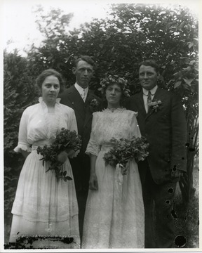 Two ladies and two gentlemen are standing together near a tree. The two ladies are holding flowers.  Possibly a wedding portrait.