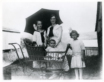 Standing from left to right: Ida Sutton, Anna Sutton, Elda Sutton, and Mable Sutton is the baby carriage.