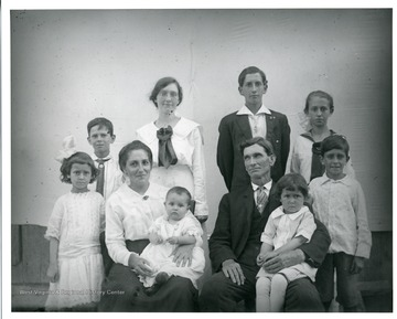 'The family of George and Bertha Teuscher Sutton. Left to right-Ida, Bill, Harley, Anna, Dave. Center row, Francis, Elda. Seated, Bertha with daughter Mable and George with son Edward. Taken on the occasion of Anna's birthday, October 07, 1918.'