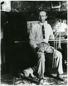 Man holding a trombone sitting beside a piano while a dog is sleeping beside him.