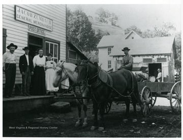 A man is sitting in a two horse-drawn wagon outside the Jacob Zumbach General Merchandise Store, on the front steps of the store, under the Post Office sign, are two ladies and two gentlemen.