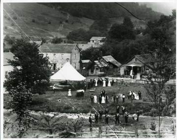 "Inscribed on the back, ""Showing the Star Band, horse-drawn 'swing' (merry-go-round), homes (l-r) Gottlief Datwlyer, cobbler shop, community store""."