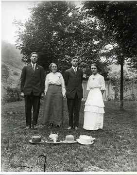 Two gentlemen wearing three piece suits are joined with two ladies wearing long dresses. Four hats are on the ground in front of them.